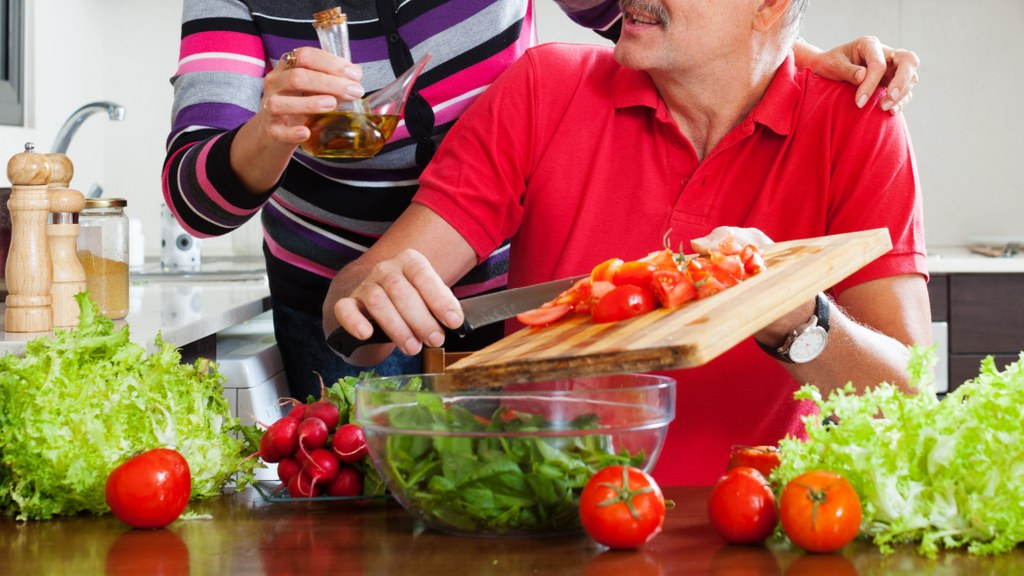 elderly couple cooking with tomatoes in home kitchen